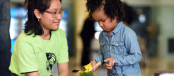 Adult volunteer engages with a young child during a school service project