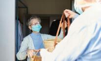 civic engagement; volunteer delivers food to senior